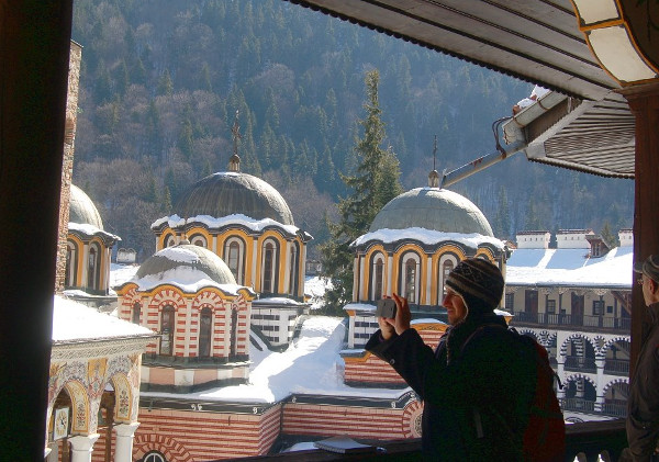 rila monastery, view from the second floor, stone walls, chapels, monastic cells, man taking a picture, forest, rila monastery tour from sofia